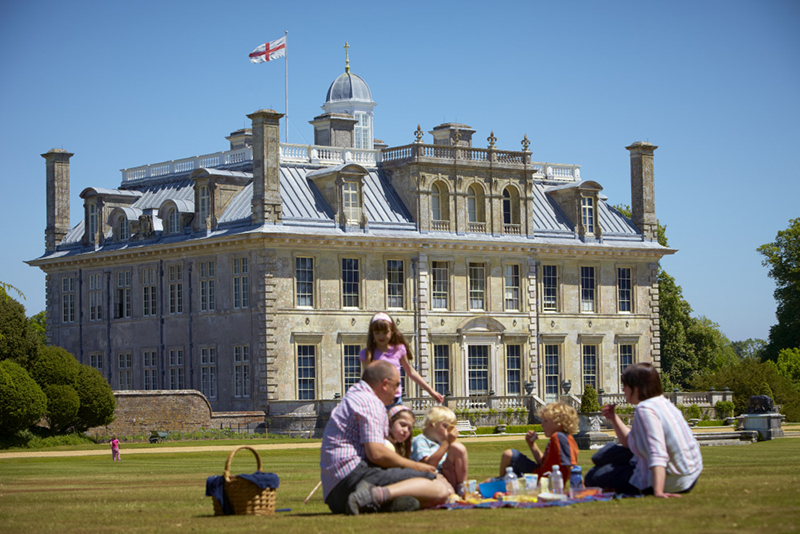 Family having a picnic on the lawn outside the house at Kingston Lacy, Dorset.