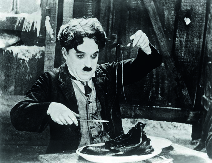 Charlie Chaplin eats his shoe in a scene from 1925 film gold Rush. Charlie Chaplin life story