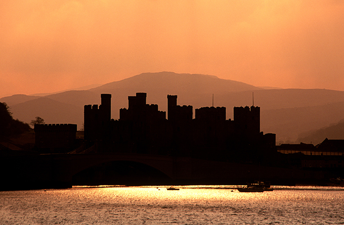 The imposing outline of Conwy castle at sunset. 12 wonders of Britain: British places everyone should visit once