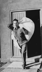 Sergeant Charles R Lahey of the Medical Corps carries a laundry bundle out fromtheofficers' quarters at Molesworth air base, 1942