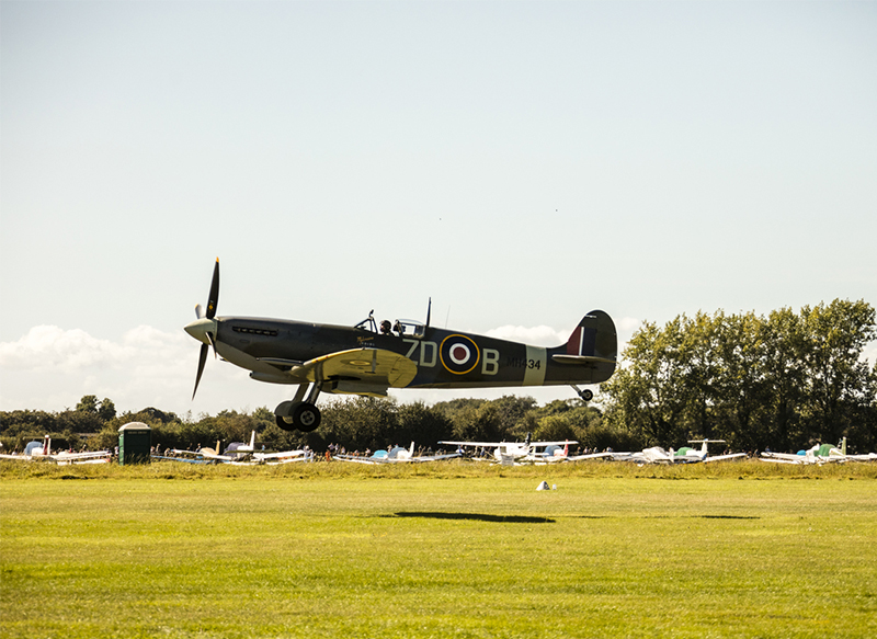 Vintage airplane during an air display at the Goodwood Revival Festival, Goodwood, England. Credit: Visit Britain