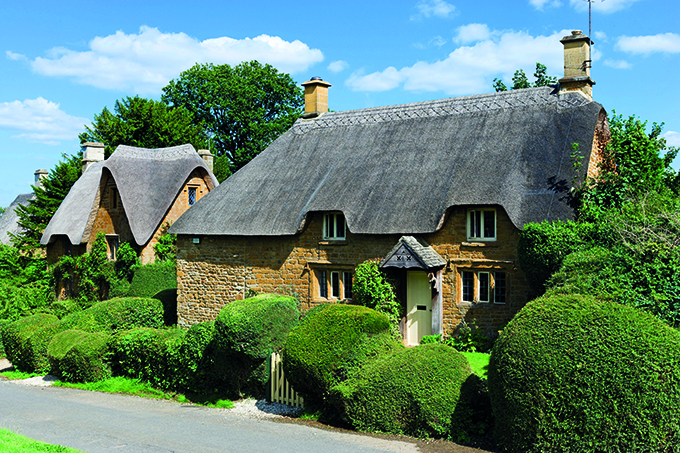 Thatched cottages in the Cotswold village of Great Tew, Oxfordshire. Credit: Ian G Dagnall/Alamy