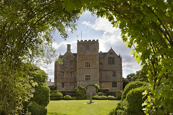 View through the Topiary Garden to the east front of Chastleton House, Oxfordshire. Credit: National Trust Images/Arnhel de Serra