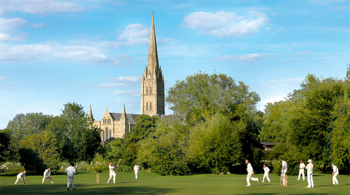A cricket match being played with Salisbury Cathedral in the background